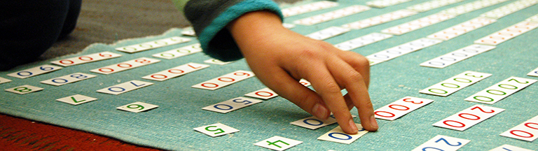 Early Childhood student works with Montessori math materials