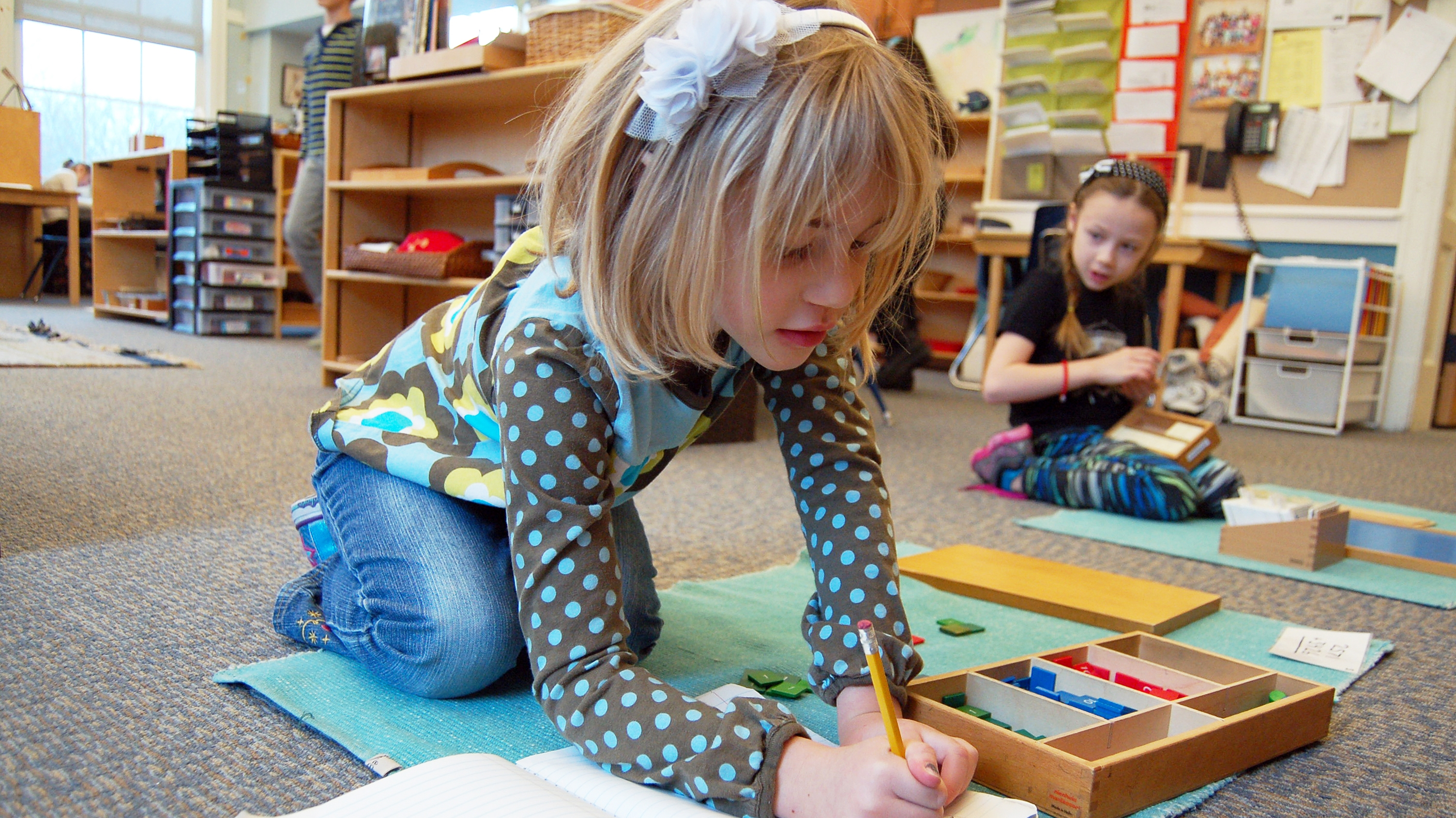 Elementary girl uses Montessori stamp game for math