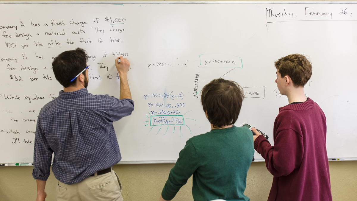 Middle School boys solve word problems on white board